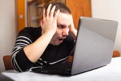 Hombre chocado con la computadora portátil Imagenes de archivo