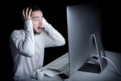 Hombre chocado con su ordenador Imagen de archivo