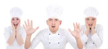 Hombre chocado divertido y dos mujeres en el uniforme del cocinero aislado en pizca Fotografía de archivo