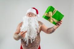 Hombre chocado en el sombrero de la Navidad que muestra el regalo Imagenes de archivo