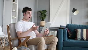 Hombre chocado en temor mientras que usa la tableta metrajes