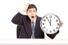 Hombre chocado en un traje, sentando y sosteniendo un reloj Foto de archivo libre de regalías