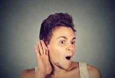 Hombre chocado entrometido con la mano al gesto del oído que escucha el chisme Imágenes de archivo libres de regalías