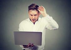 Hombre chocado feliz con noticias en el ordenador portátil imágenes de archivo libres de regalías
