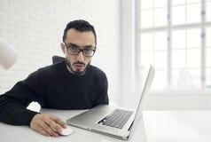 Hombre chocado mientras que trabaja en el ordenador en oficina Fotografía de archivo