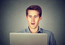 Hombre chocado que mira el ordenador portátil Foto de archivo