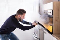 Hombre chocado que mira las galletas quemadas en horno foto de archivo libre de regalías