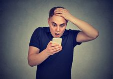 Hombre chocado que mira su teléfono móvil que ve el mensaje de texto de la lectura de las malas noticias foto de archivo libre de regalías