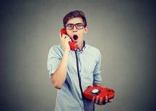 Hombre chocado que recibe malas noticias en el teléfono Foto de archivo libre de regalías