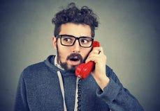 Hombre chocado que recibe noticias inesperadas sobre el teléfono Fotos de archivo libres de regalías