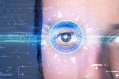 Hombre cibernético con el ojo technolgy que mira en el iris azul Fotografía de archivo