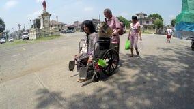Hombre ciego que empuja la silla de ruedas del mendigo discapacitado almacen de metraje de vídeo