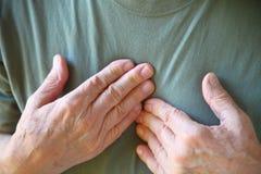 Hombre con ambas manos en pecho fotografía de archivo