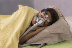 Hombre con apnea durmiente y la máquina de CPAP Foto de archivo libre de regalías