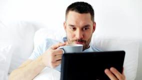 Hombre con café de consumición de la PC de la tableta en cama en casa almacen de metraje de vídeo