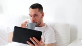 Hombre con café de consumición de la PC de la tableta en cama en casa almacen de video