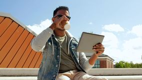 Hombre con café de consumición de la PC de la tableta en el top del tejado almacen de video
