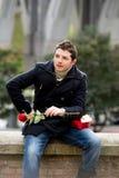 Hombre con chocolates y una rosa que es levantada Imagen de archivo libre de regalías