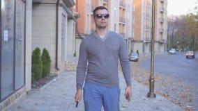 Hombre con deficiencias visuales en vidrios con un bastón en la ciudad del otoño metrajes
