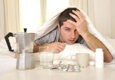 Hombre con dolor de cabeza y resaca en cama con las tabletas Imagen de archivo libre de regalías