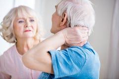 Hombre con dolor de cuello y mujer en cuestión en casa Fotos de archivo libres de regalías