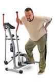 Hombre con dolor de espalda cerca de un dispositivo de entrenamiento Imagen de archivo