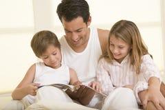 Hombre con dos niños jovenes que se sientan en la lectura de la cama Fotos de archivo