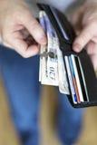 Hombre con efectivo dentro de la cartera Imágenes de archivo libres de regalías