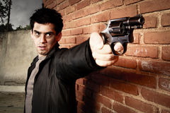 Hombre con el arma en un callejón Fotografía de archivo libre de regalías