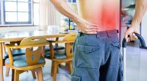 Hombre con el bast?n y el dolor de espalda terrible imágenes de archivo libres de regalías