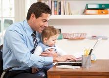 Hombre con el bebé que trabaja de hogar usando la computadora portátil Foto de archivo libre de regalías