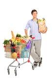 Hombre con el bolso al lado de un carro de compras Imágenes de archivo libres de regalías