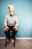 Hombre con el bolso de arriba en silla Fotos de archivo