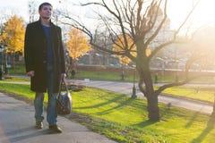 Hombre con el bolso en el camino en parque Imagen de archivo