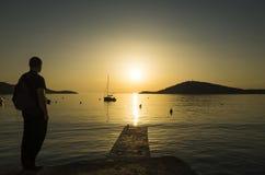 Hombre con el bolso en la situación trasera en puesta del sol en el mar adriático en Croacia Imagen de archivo libre de regalías