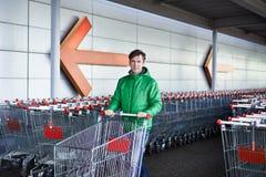 Hombre con el carro de la compra en el estacionamiento Foto de archivo libre de regalías