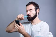 Hombre con el cepillo de dientes y Smartphone Fotografía de archivo