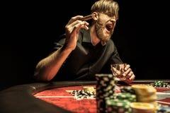 Hombre con el cigarro y el vidrio que se sientan en la tabla del póker y que gritan Fotografía de archivo libre de regalías