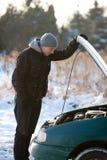 Hombre con el coche quebrado en invierno Foto de archivo libre de regalías