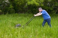 Hombre con el cortacésped que siega la hierba alta y el césped grande, grande Imágenes de archivo libres de regalías