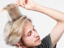 Hombre con el corte de pelo elegante que se peina el pelo Imagenes de archivo