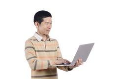 El ordenador portátil del uso del hombre conecta Internet Fotografía de archivo libre de regalías