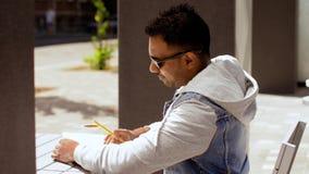 Hombre con el cuaderno y el café en el café de la calle almacen de video