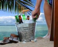 Hombre con el cubo de la cerveza en la playa Imagen de archivo
