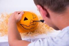 Hombre con el cuchillo que prepara la calabaza para Halloween Fotos de archivo