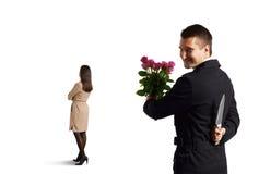 Hombre con el cuchillo que se coloca detrás de mujer Fotos de archivo