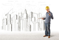 Hombre con el dibujo de la ciudad del edificio en fondo Foto de archivo libre de regalías