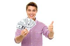 Hombre con el dinero que muestra los pulgares para arriba Foto de archivo