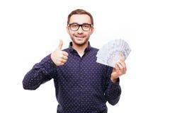 Hombre con el dinero que muestra los pulgares para arriba aislados en blanco Imagenes de archivo
