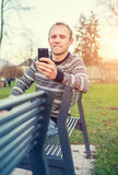 Hombre con el dispositivo móvil en parque del otoño Imagen de archivo